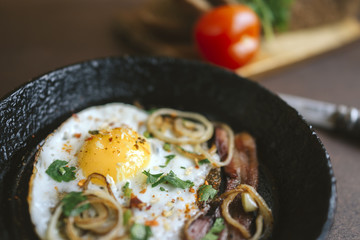 fried egg, bacon, onion rings, parsley - tasty Breakfast or snack, in the old pan on a dark wooden background.
