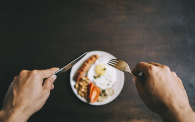 Male hands holding silver cutlery over out of focus plate, on the plate there is fried egg with sausage
