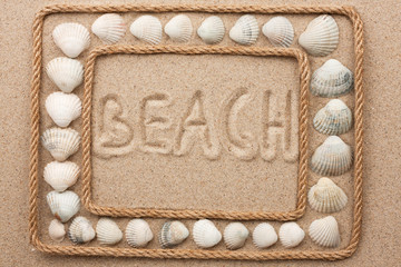 Beautiful frame of rope and seashells on the sand with inscription beach