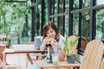 asia girl hold yellow camera in the coffee shop