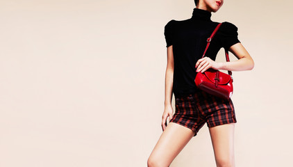 Wall Mural - Black top and red plaid shorts woman holding red hangbag isolated on brown background. with copy space.
