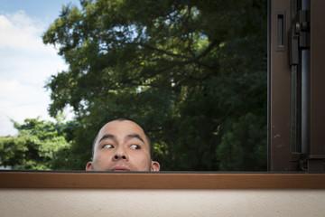 窓から覗く男性