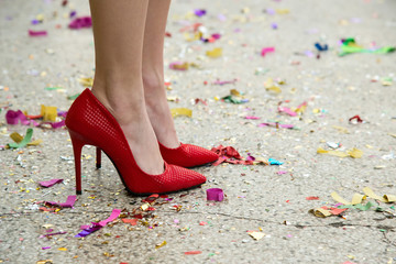 female legs in red shoes against the confetti and garlands