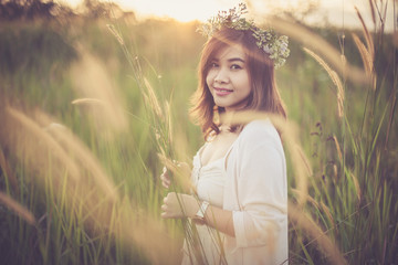 Young asian woman posing in golden field on sunset