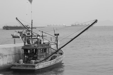 Old fishing boat in the sea in white and black tone