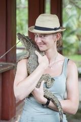 junge Frau hält Krokodil im Arm, Kaiman in Kuba