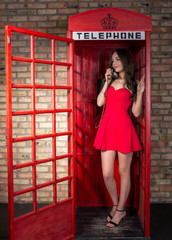 Young woman in a short red dress talking on the phone