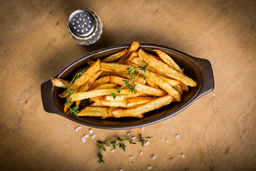 Potatoes fries in the bowl with salt and thyme