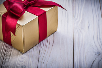 Present box with red knot on wooden board holidays concept