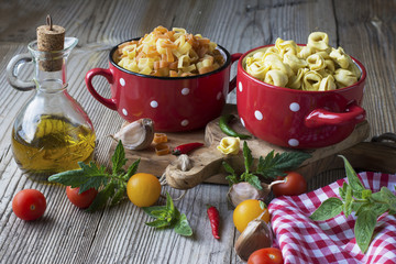 Still life Italian pasta. Tortellini in the form of hearts on a cutting board with olive tree