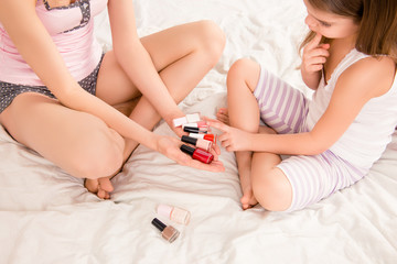 Close up portrait of little girl choosing varnish for manicure
