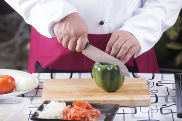 Chef cutting green bell pepper with knife before cooking