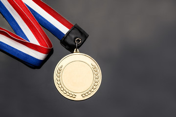 Generic sporting event gold medal with red and blue ribbon