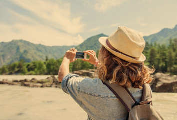 Young woman traveler on a background of mountains takes photos o