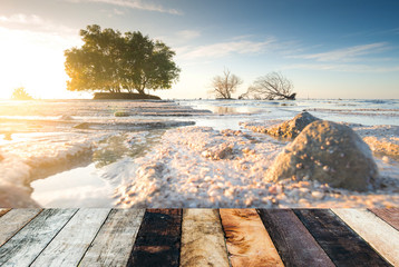 Empty top of wooden decking and view of tropical beach background, blue sea, white sand beach with clear blue sky background and,mock up, Sunset with sun rays, sky with clouds and sun.