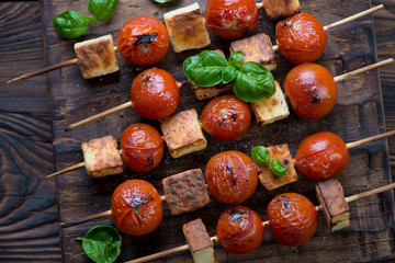 Grilled cherry tomatoes and cheese on skewers, top view, closeup
