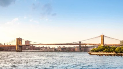 Fototapete - Timelapse with Brooklyn Bridge in transition between day and night, in New York City. Clouds invade the sky, while boats crisscross East River.