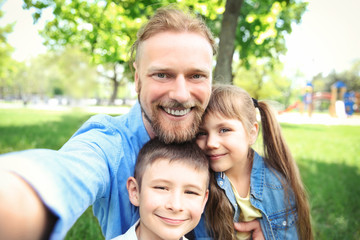 Happy family taking selfie in the park