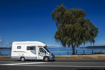 A campervan driving along the coast of Lake Taupo in North Island of New Zealand