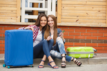 two young women-a brunette with long straight hair,with blue and green suitcase sitting in front of the station and reading text message on smartphone