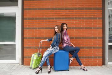 two young women-a brunette with long straight hair,dressed in blue jeans,a white tee,plaid shirt and blue jacket with blue and green suitcase sitting in front of the station on the blue suitcase