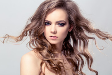 Portrait of young beautiful girl with flying hair. Fashion photo