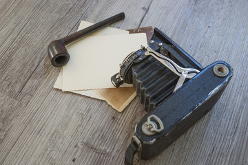 Old retro camera with tobacco pipe on vintage wooden board