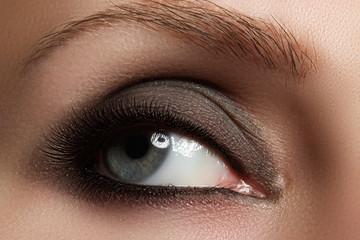 Macro shot of woman's beautiful eye with extremely long eyelashes. Sexy view, sensual look. Fashion smoky makeup.