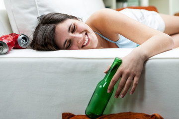 Happy drunk young woman relaxing on a sofa