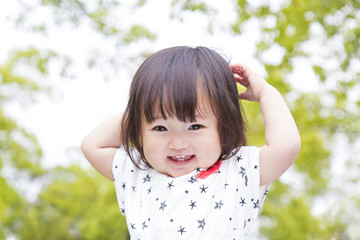 新緑の中、微笑む幼い女の子