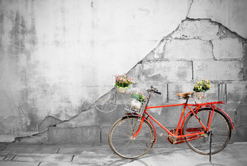 Red bicycle on Old brick wall background.