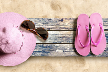 Summer beach accesories on old wooden boards on the sand beach