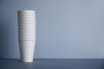 Many white paper cups folded one in other in big bunch, isolated on left on simple gray background