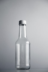 Empty unlabeled glass transparent bottle isolated on gray background in center