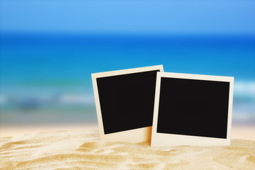 Beach with blank instant photos in front of summer sea backgroun
