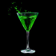 a glass of absinthe on black background