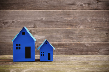 A paper houses stands over a wooden background