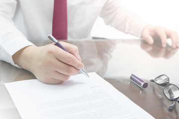 Businessman is signing a contract, business contract details. Or businessman rigning on a resignation letter concept.