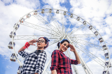 Two friends posing in camera with ferris wheel in background