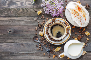 Rustic wooden background with cup of coffee, milk, meringue with peanuts and lilac flowers. White vintage dinnerware and spoon. Breakfast at summer morning. Top view, place for text.