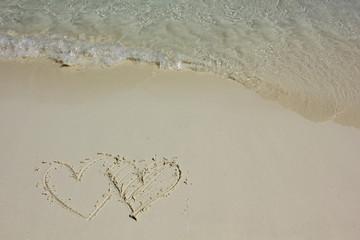 Heart shapes on white sand beach