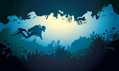 Silhouette of underwater cave with diver and coral reef.
