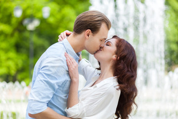 Passionate romantic young couple kissing and embracing in a green park