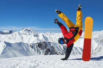 Man standing on hand upside down near snowboard