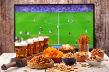 Beer and snacks set on football match tv background