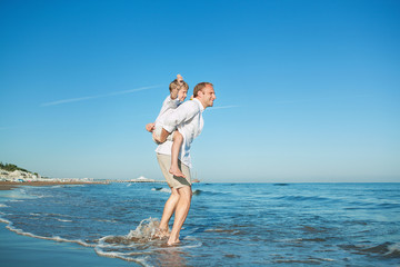 Father with son playing together on sea surf line