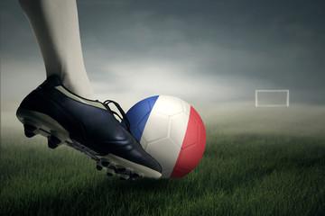 Soccer player kicking ball toward a goal post