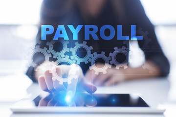 """Woman is using tablet pc, pressing on virtual screen and select """"Payroll""""."""