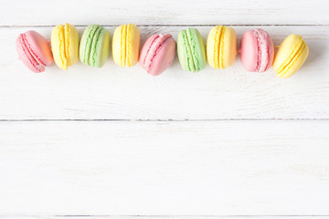 multicolored macaroon on white wooden background, flat lay, top view