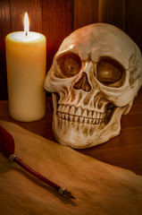 Candle lit scene of a skull, aged paper with a pentagram wax seal on it and a red feather fountain pen